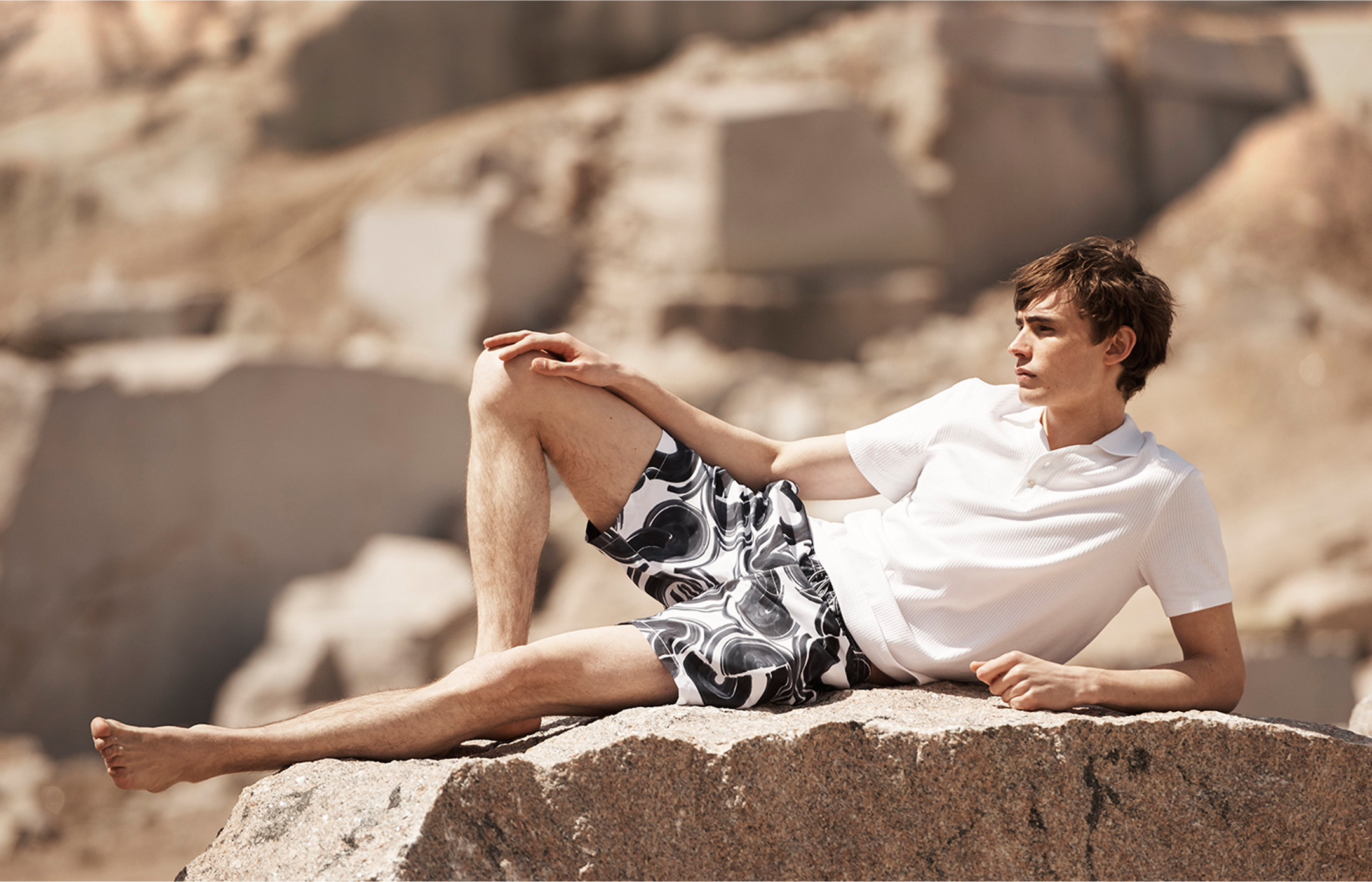 A man lies on a rock outside in patterned swim shorts and a white polo shirt.