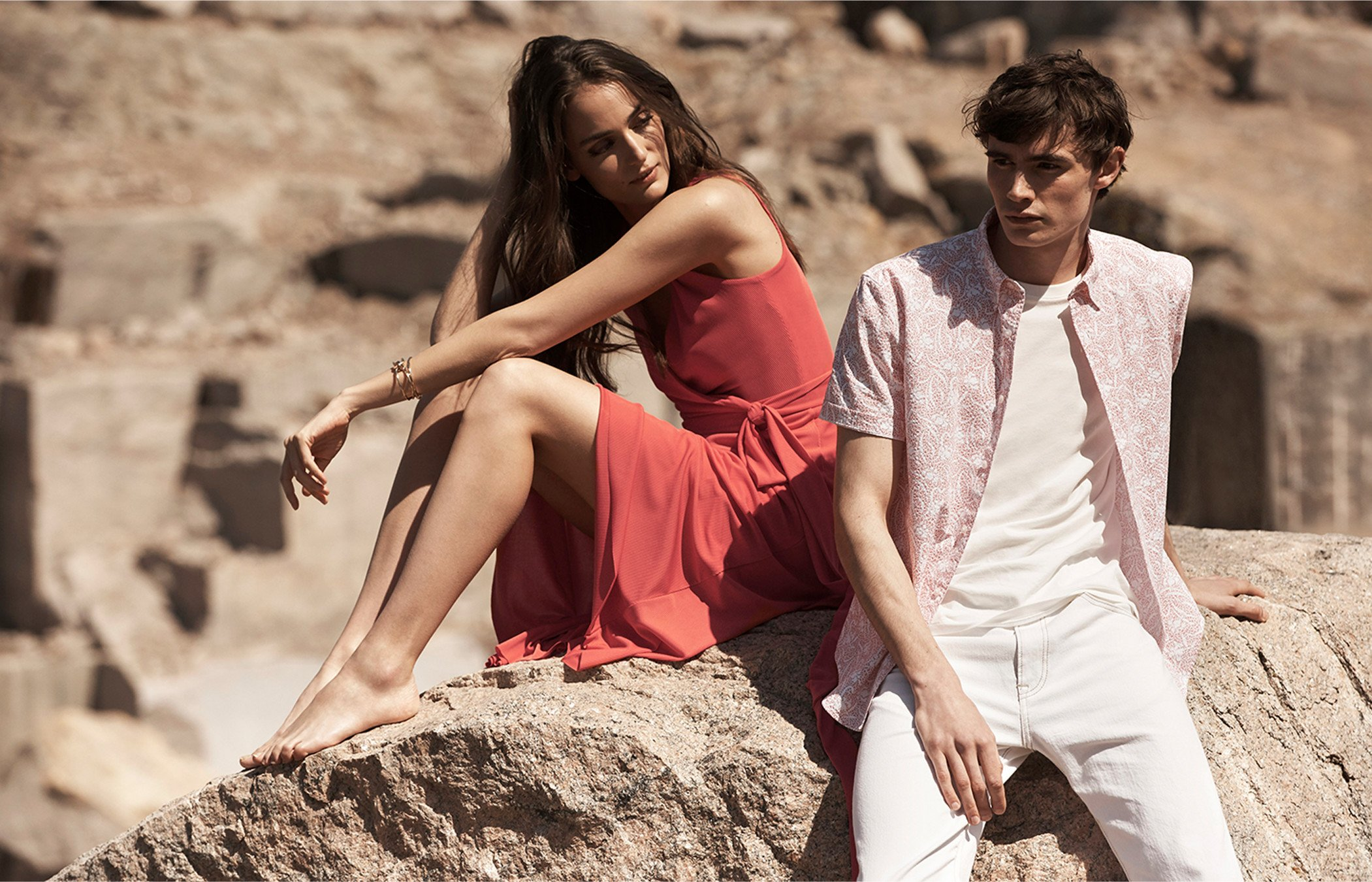 A man and a woman in lightweight summer clothing sit outside in the sun.