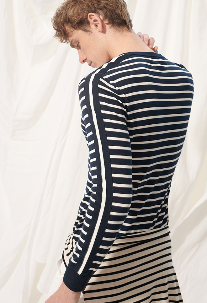 Man in striped crewneck sweater.