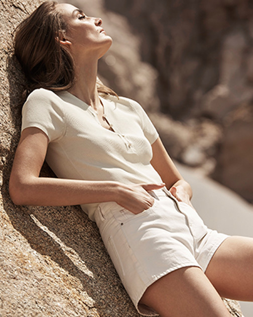 A woman lies in the sun in a knit shirt and cream-colored jean shorts.
