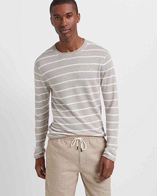 A man in a pair of khakis and a linen striped sweater.
