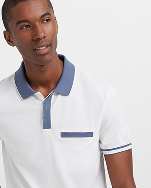 A man wears a white polo shirt with blue tipping.