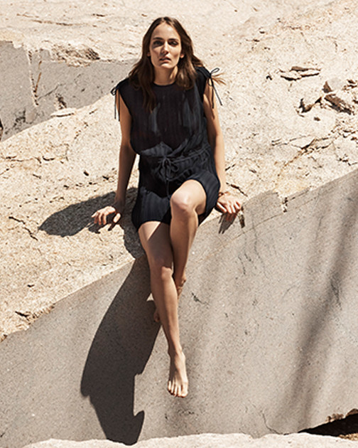 A woman sits outside wearing a black romper.