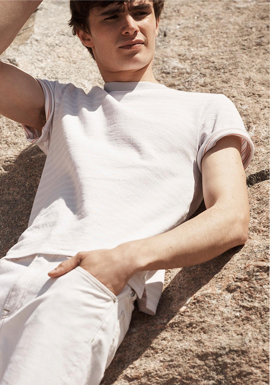 A man lies in the sun wearing bone denim and a striped t-shirt