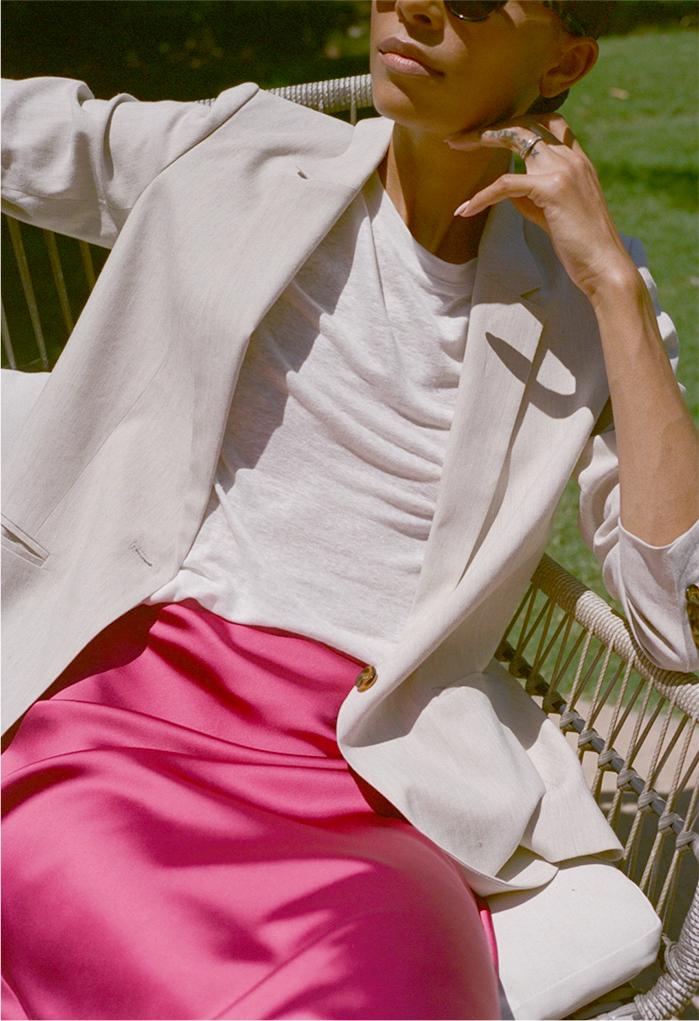 Woman in silky skirt, linen crewneck tee, and linen blazer