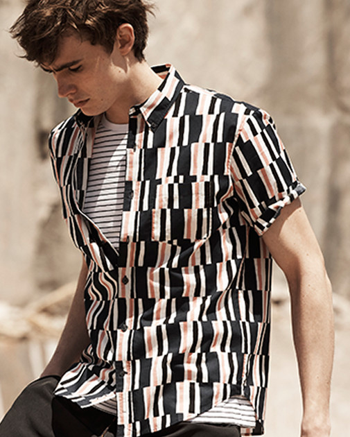 A man wears a patterned button-down shirt over a striped t-shirt.