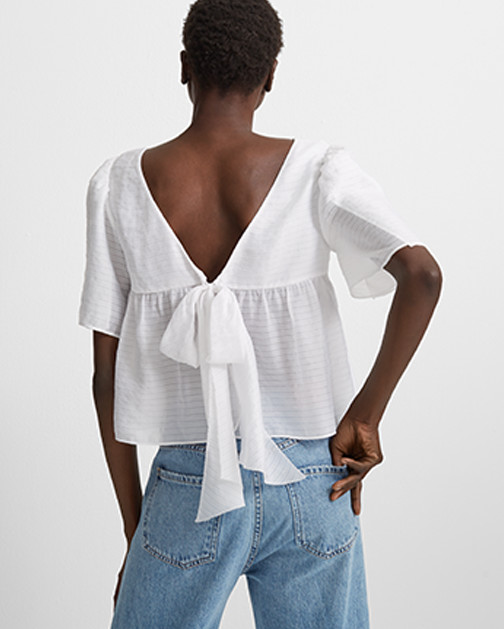 A woman is shown from behind in a breezy, open-back summer shirt.